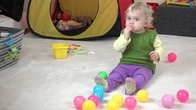 Baby girl eat cookie and play with colorful balls in play room. stock video footage