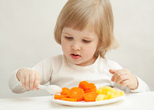 The baby girl is eating Stock Images