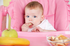 Baby girl eating alone Royalty Free Stock Images