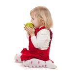 Baby girl eating apple stock photo