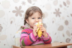 Baby girl eating banana. With face expression Royalty Free Stock Photo