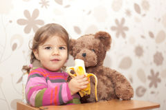 Baby girl eating banana. With face expression Stock Images
