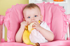 Baby girl eating a banana Royalty Free Stock Photos