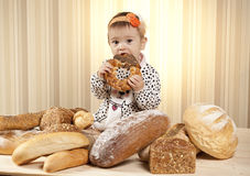 Baby girl eating bread. White infant eating bread from basket Royalty Free Stock Image