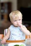 Baby girl eating broccoli Stock Photography