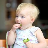 Baby girl eating broccoli Stock Images