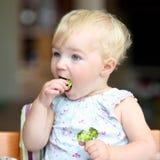 Baby girl eating broccoli Stock Images