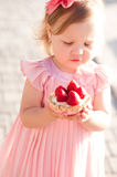 Baby girl eating cake outdoors Royalty Free Stock Photography