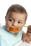 Baby girl is eating carrots from a spoon Stock Photo