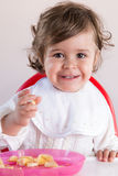 Baby girl eating fruit stock photos