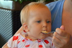 A baby girl eating gomogenised food from the spoon Royalty Free Stock Image