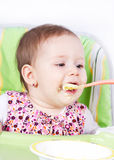 Baby girl eating in her chair Royalty Free Stock Photography