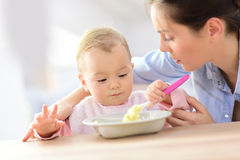 Baby girl eating with her mother Royalty Free Stock Image