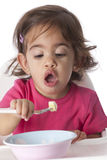 Baby girl is eating by herself Stock Photos
