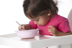 Baby girl is eating by herself Royalty Free Stock Photography