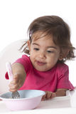 Baby girl is eating by herself Stock Photography