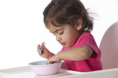 Baby girl is eating by herself Royalty Free Stock Image