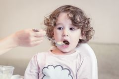 Baby girl during eating at home royalty free stock photos