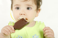 Baby girl eating an ice cream mini Stock Photography