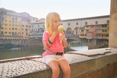 Baby girl eating ice cream near ponte vecchio Stock Photos