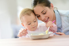 Baby girl eating lunch. With help of her mommy stock photography