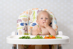 Baby girl eating raw food. Baby girl sitting in a highchair eating raw, seasonal vegetables: carrots, beans, peas, celery Stock Photography