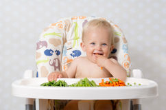 Baby girl eating raw food Royalty Free Stock Images