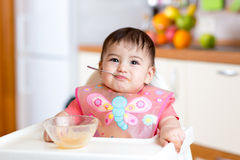 Baby girl eating with spoon and sitting in a high chair for feeding Stock Images