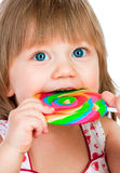 Baby girl eating a sticky lollipop Royalty Free Stock Photography