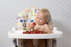 Baby girl eating strawberries. Baby girl sitting in a highchair eating fresh strawberries Stock Photo
