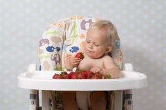 Baby girl eating strawberries Stock Photo
