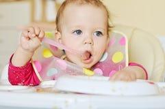 Baby girl is eating Stock Photo