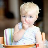Baby girl eating tomatoes Royalty Free Stock Photography