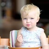 Baby girl eating tomatoes Royalty Free Stock Photo