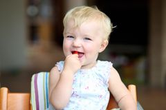 Baby girl eating tomatoes Stock Images