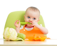 Baby girl eating vegetables Stock Images