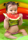 Baby girl eating watermelon. In wading pool Stock Photo