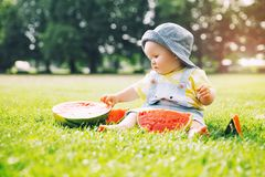 Baby girl eating watermelon on green grass in summertime on natu Stock Photography