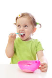 Baby girl eating yoghurt Royalty Free Stock Images