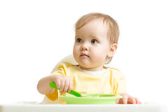 Baby girl eating yogurt or puree isolated on white background Stock Photos