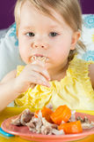 Baby girl eats hands chicken with carrots. On childrens table stock images