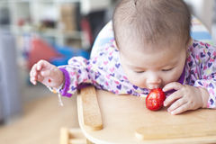 Baby girl eats at the high chair Royalty Free Stock Photo