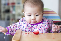Baby girl eats at the high chair Stock Photo