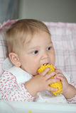 Baby girl eats sweet corn Royalty Free Stock Images