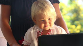 Baby Girl in Embroidery Dress Watching Cartoon Closeup. Small blonde baby girl in embroidery dress watching cartoon based on her mother closeup stock footage