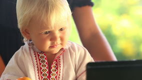 Baby Girl in Embroidery Dress Watching Cartoon Closeup. Small blonde baby girl in embroidery dress hold ball and watching cartoon closeup stock video footage