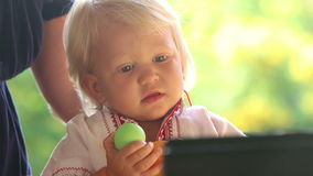 Baby Girl in Embroidery Dress Watching Cartoon Closeup. Small blonde baby girl in embroidery dress hold ball and watching cartoon closeup stock footage