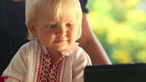 Baby Girl in Embroidery Dress Watching Cartoon Closeup. Small blonde baby girl in embroidery dress watching cartoon and picks up a small globe closeup stock footage