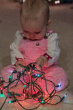 Baby girl explores christmas lights string Royalty Free Stock Photography