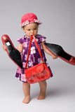 Baby Girl Fashion. Funny shot of one year old fashion girl with red purse and big adult shoes stock image